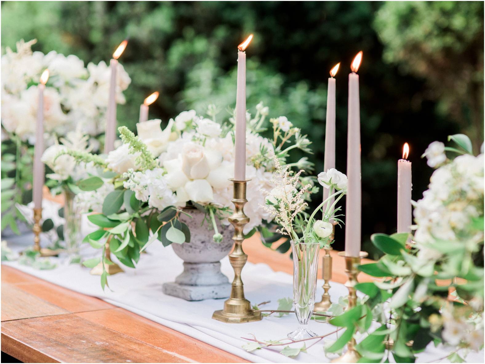 Taupe tall candles in gold brass votives line a tablescape in manicured gardens of cranberry creek gardens
