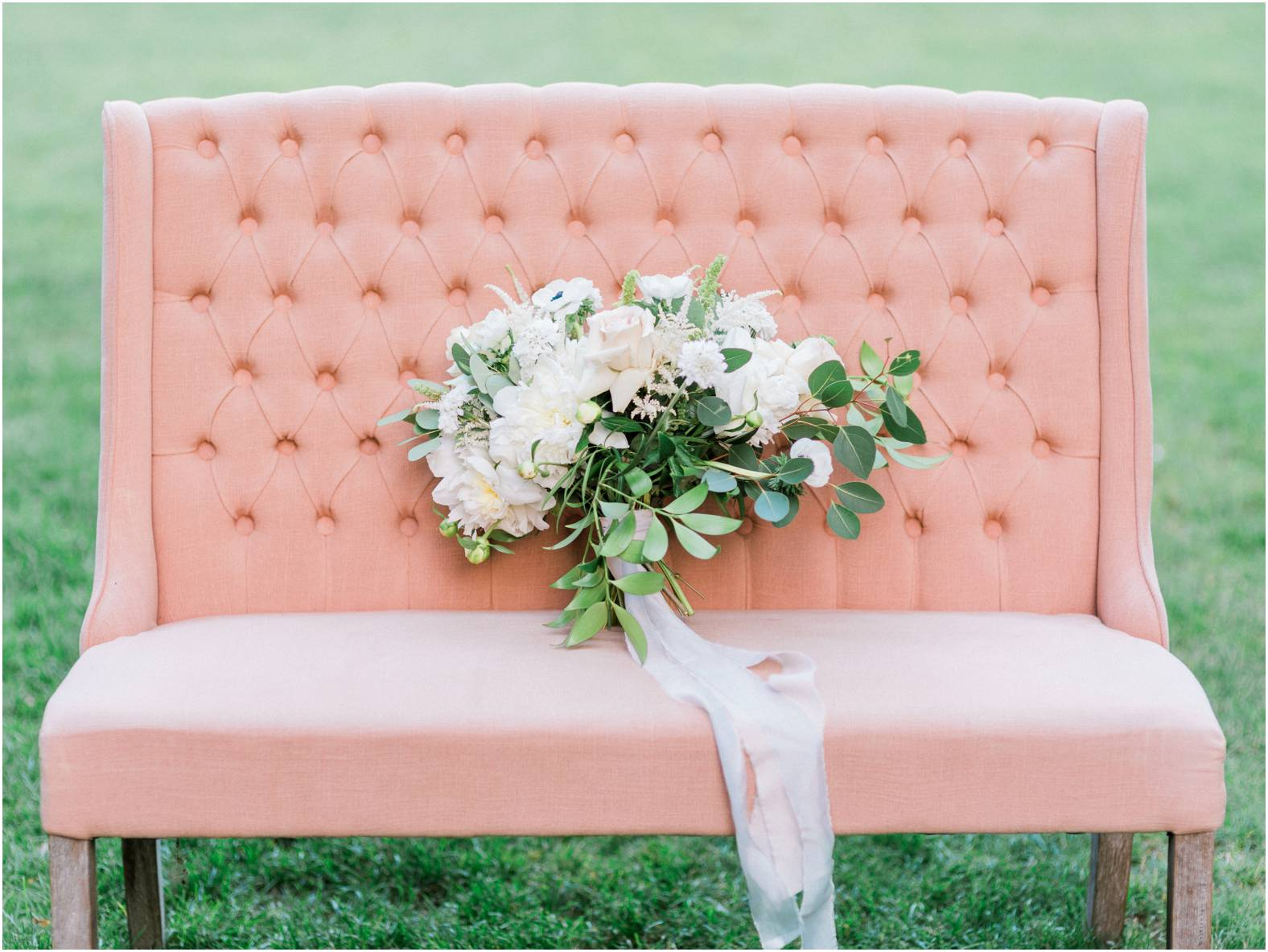Loose neutral bouquet with anemone blooms sits on a blush linen sofa by Warehouse 84