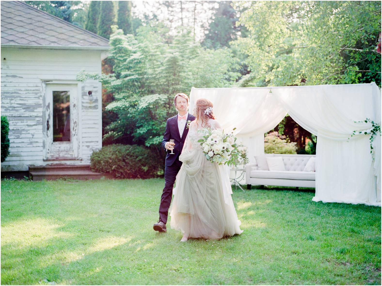 bride and groom walk away from draped private lounge during intimate garden wedding in ontario