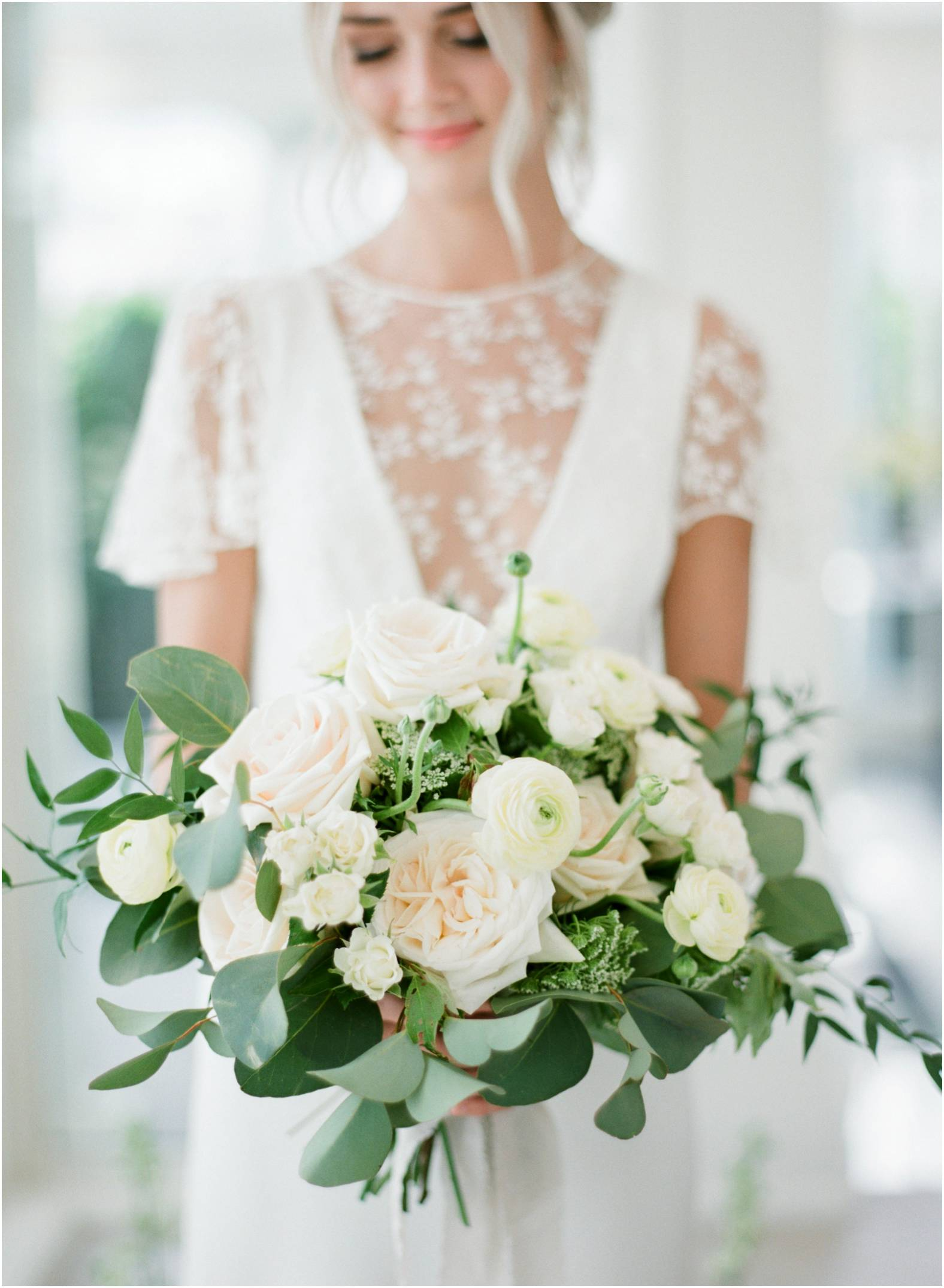 Bride wearing lace dress from The Modern Bride with bright coral lipstick and low classic updo holds a large loose bouquet of neutral blooms and greenery during her outdoor garden wedding at The Gate House in Niagara on the Lake