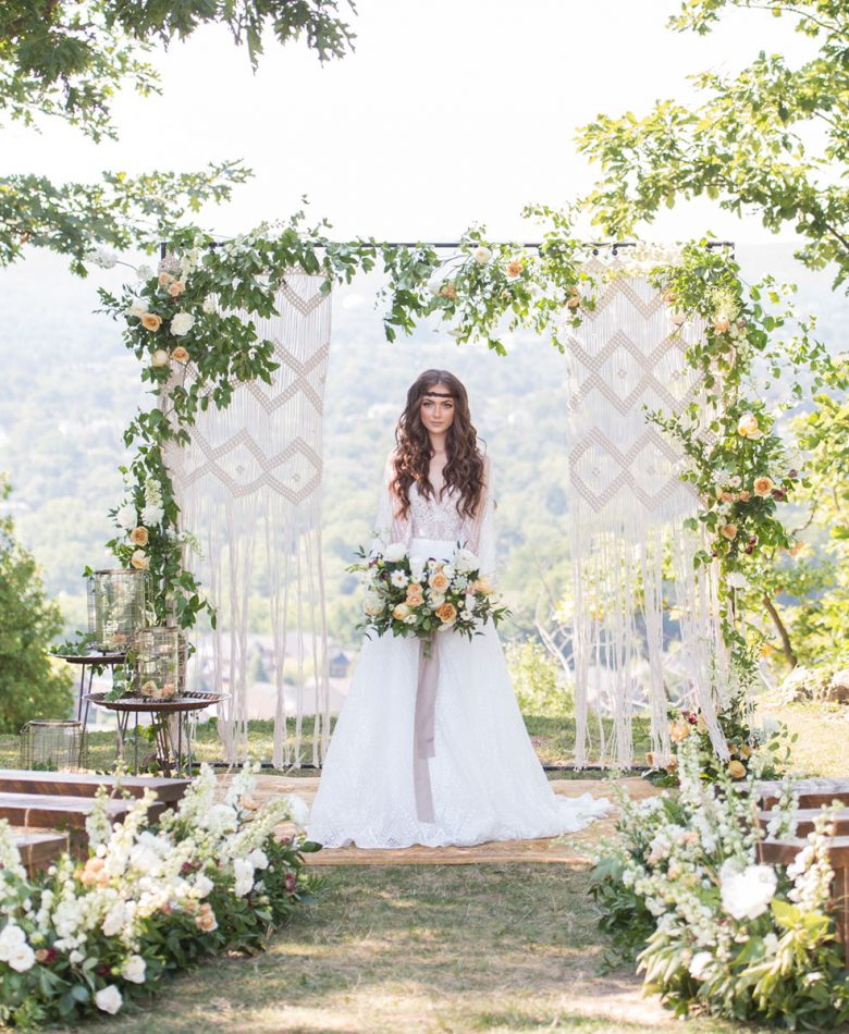 A boho bride standing in an outdoor ceremony setting with a macrame and floral backdrop