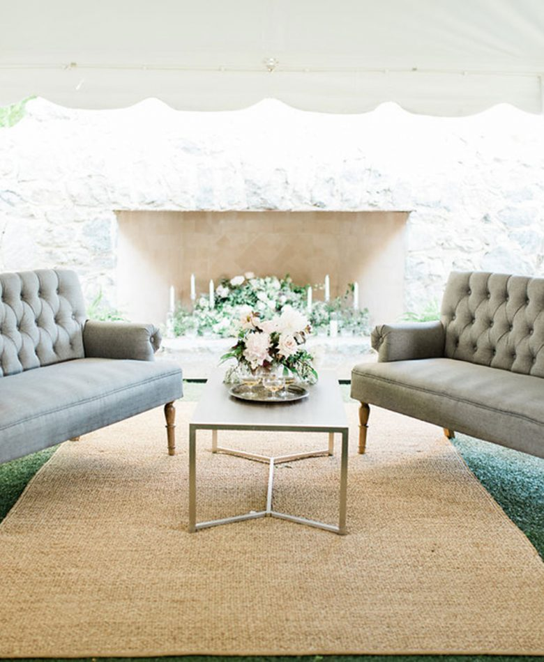 A lounge area for a wedding inside a tent with two couches
