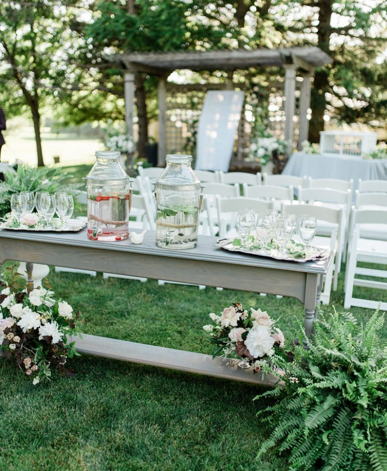 A garden themed wedding ceremony with a refreshment table for guests