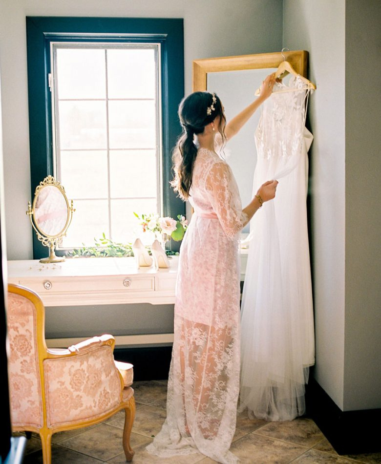 A bride hanging up her wedding dress in an intimate bridal lounge