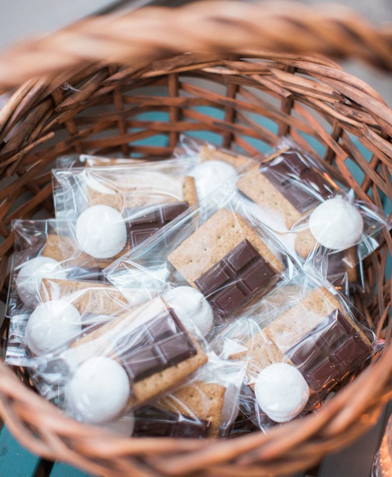 Backyard party with a basket full of ingredients to make s'mores