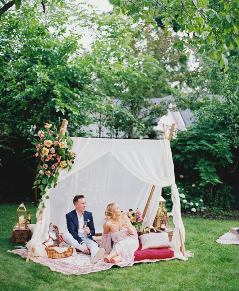 A backyard wedding party with a white teepee and picnic