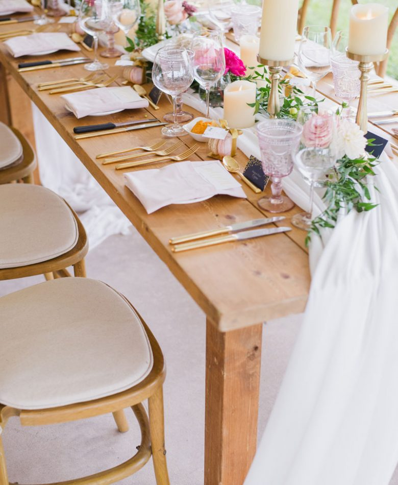 A closeup of a table setting with gold candles and blush floral accents