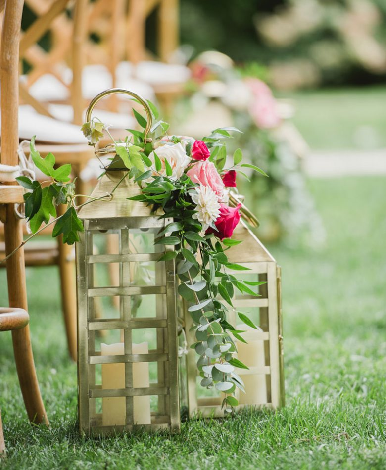 Gold lanterns with blush floral accents along the aisle for a wedding