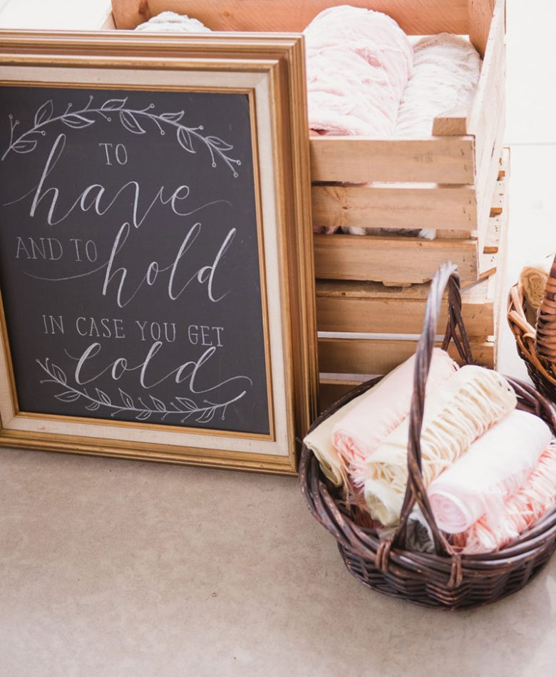 A frame describing to have and to hold in case you get cold, next to a basket with pashmina scarves