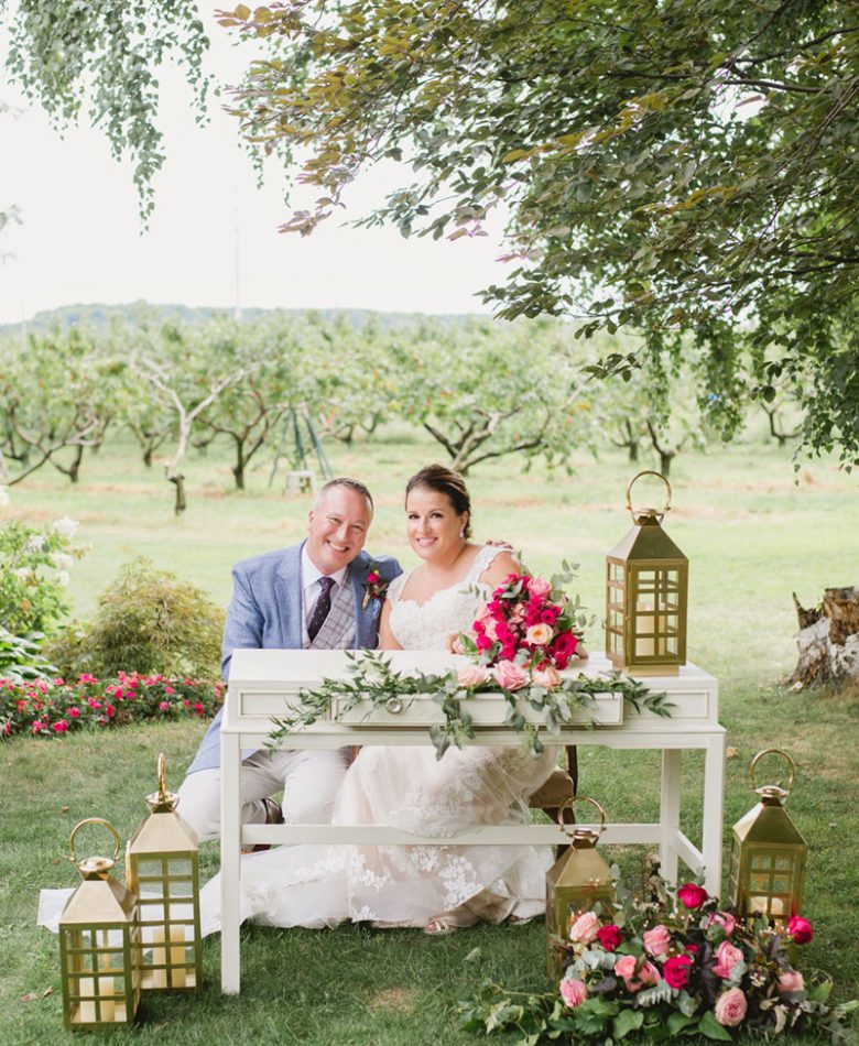 A smiling bride and groom sitting at a sweetheart table in an orchard setting and blush decor accents