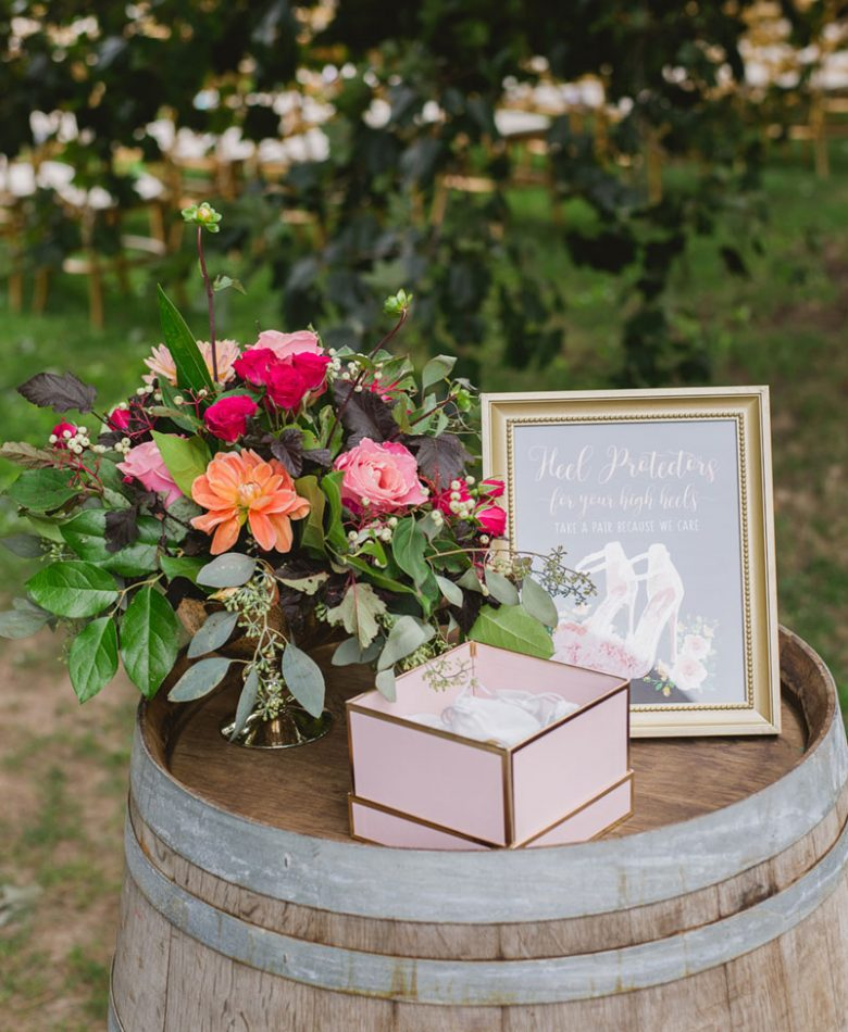 A wine barrel with a bouquet of orange, pink and blush florals, a frame and a blush box on top