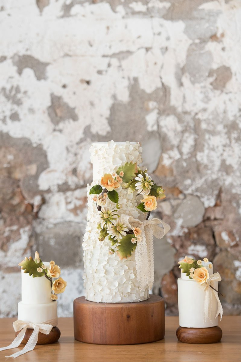 Boho themed white wedding cakes on wooden cake stands