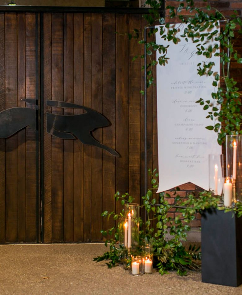 A candlelit wedding industrial frame that is displaying a welcome sign