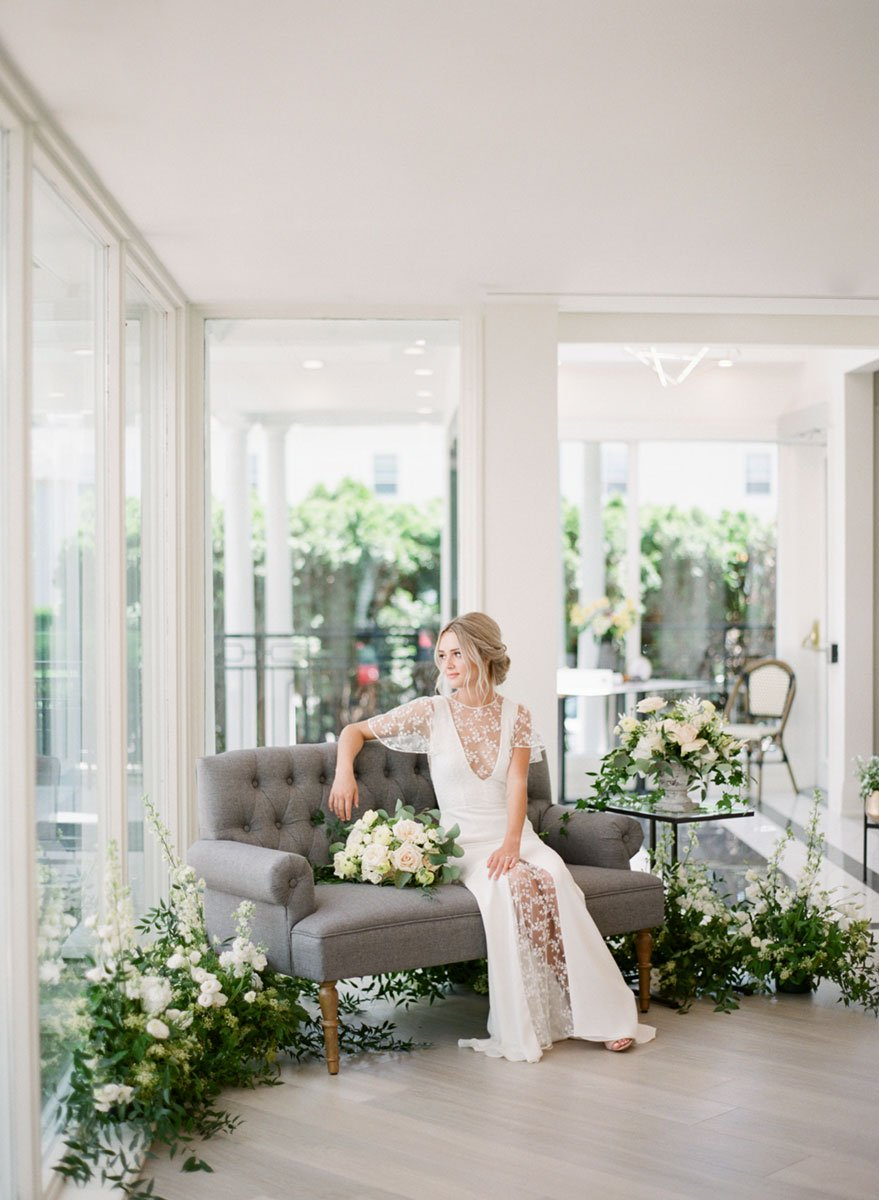 A bride sitting on a grey lounge, in a classic white wedding setting