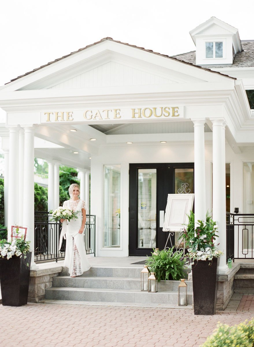A bride standing in front of The Gate house in Niagara with gold lanterns along the steps