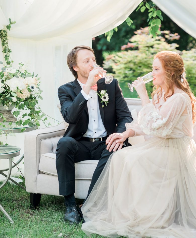 Bride and groom sitting on a light grey lounge in a tent amidst a garden