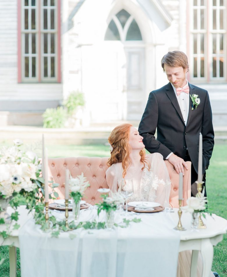 Bride and groom at a sweetheart table amidst a garden