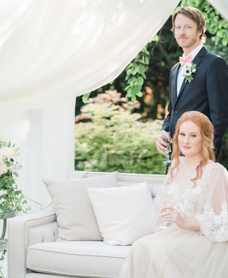 Bride sitting on a light grey lounge in a tent amidst a garden with a groom standing behind her