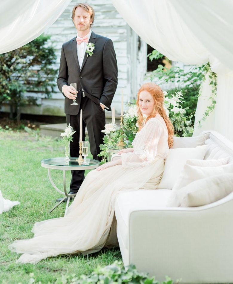 Bride sitting on a light grey lounge in a tent amidst a garden