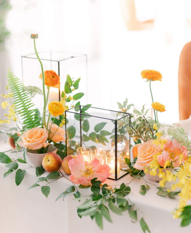 Candle centrepiece with peach and floral accents