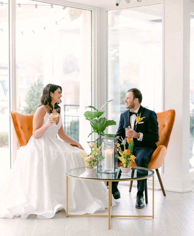 Peach summer wedding cocktail lounge with bride and groom sitting in orange chairs