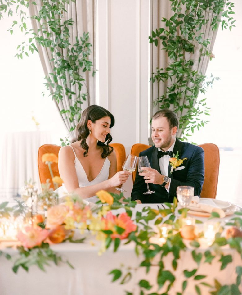 Peach summer wedding sweetheart table with two orange wingback chairs