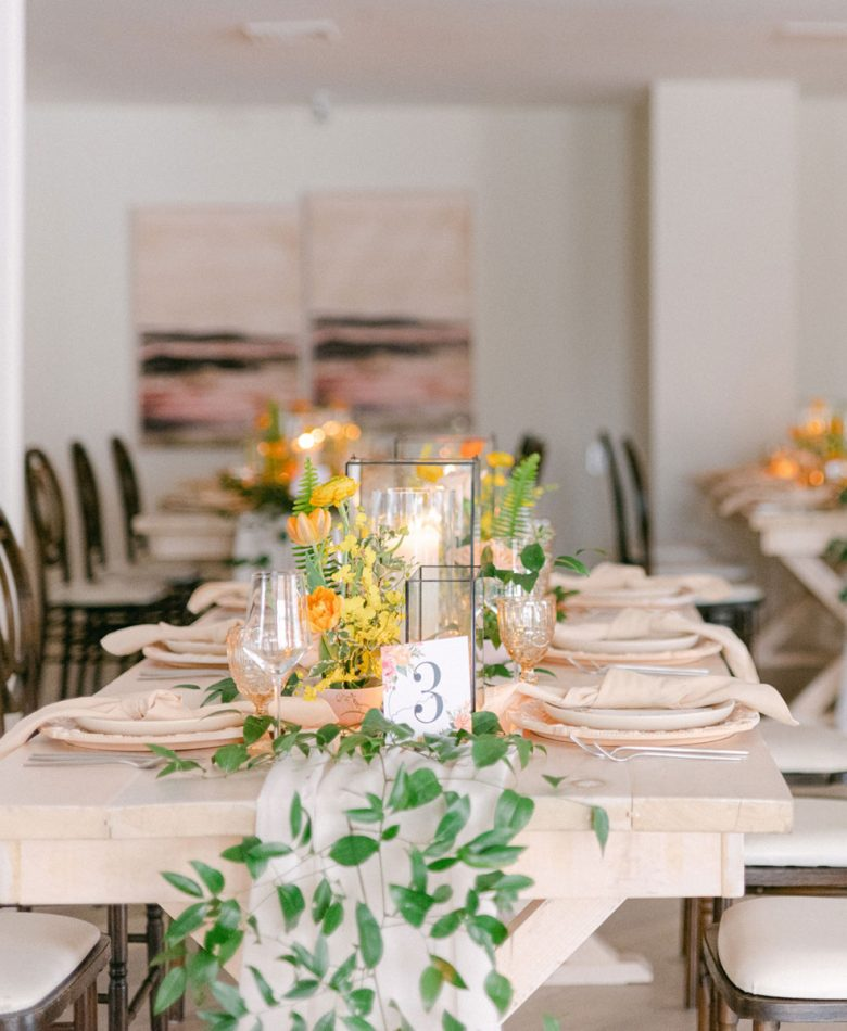 A wedding reception table set with candles, peach decor and accents.