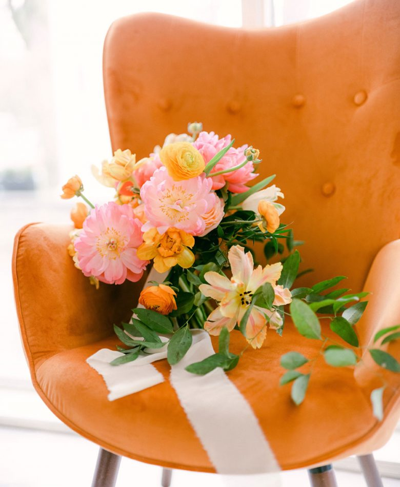Peach summer wedding with an orange wingback char and a large pink and orange bouquet