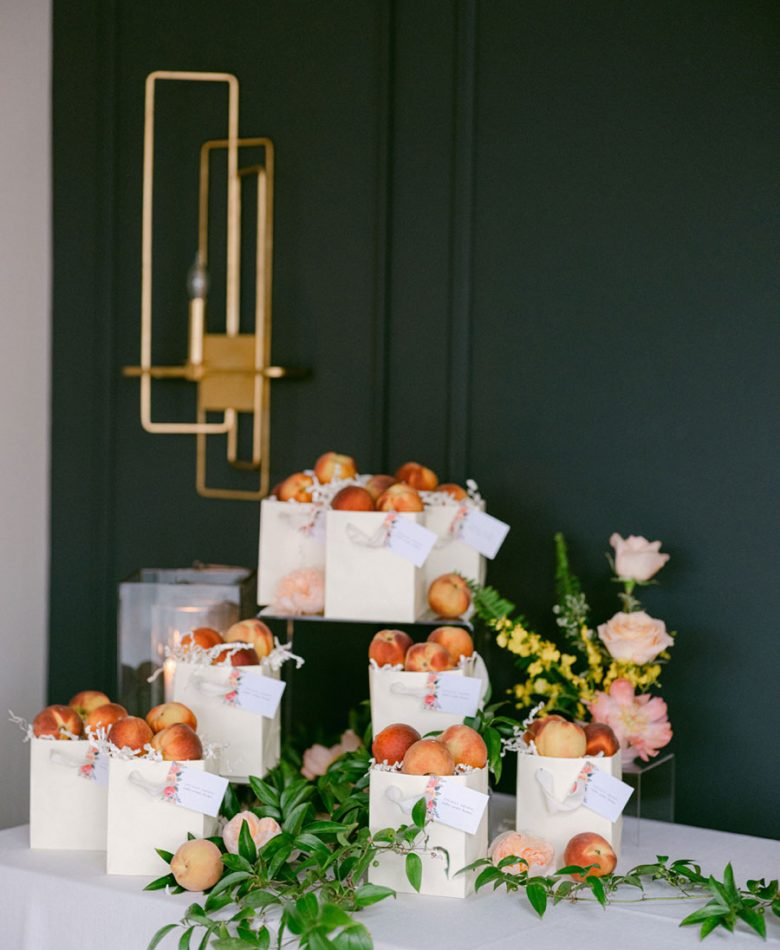 Peach summer wedding welcome table with boxes of peaches