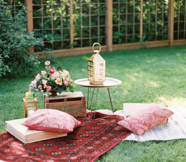Backyard party with a picnic setup of pillows and blankets