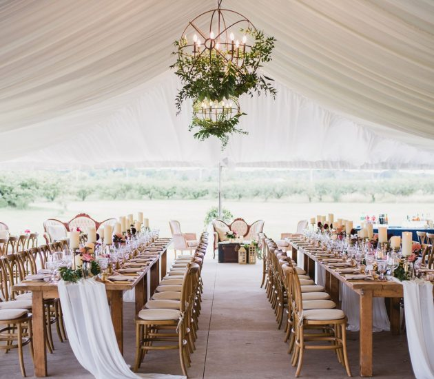 A wedding reception set up in a tent outdoors with candles and blush decor accents