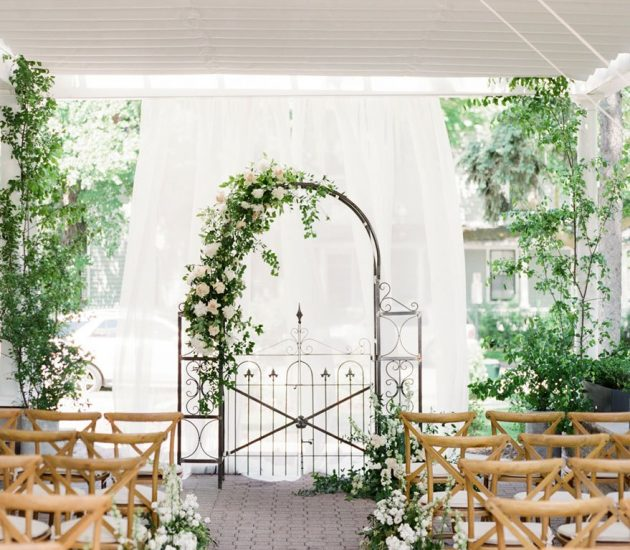 Classic white wedding theme ceremony arch with white and green florals
