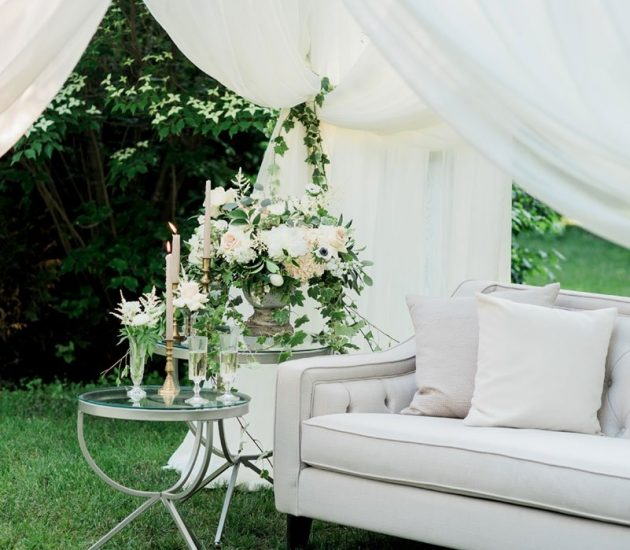 Grey and linen lounge in a tent with a garden